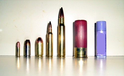 Comparison of different common ammunition sizes. Left to right: .22 LR hollow point, 9mm Parabellum hollow point, .45, .223 PMC bronze 55 grain FMG Boat Tail, 30-06 American Eagle Federal 150 g FMG Boat Tail, 12-gauge shotshell (00 Buckshot), and lip gloss for size comparison.
