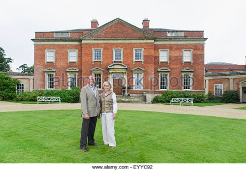 caucasian-couple-smiling-outside-mansion-eyyc92