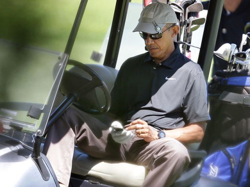 obama-in-golf-cart-on-phone-ap